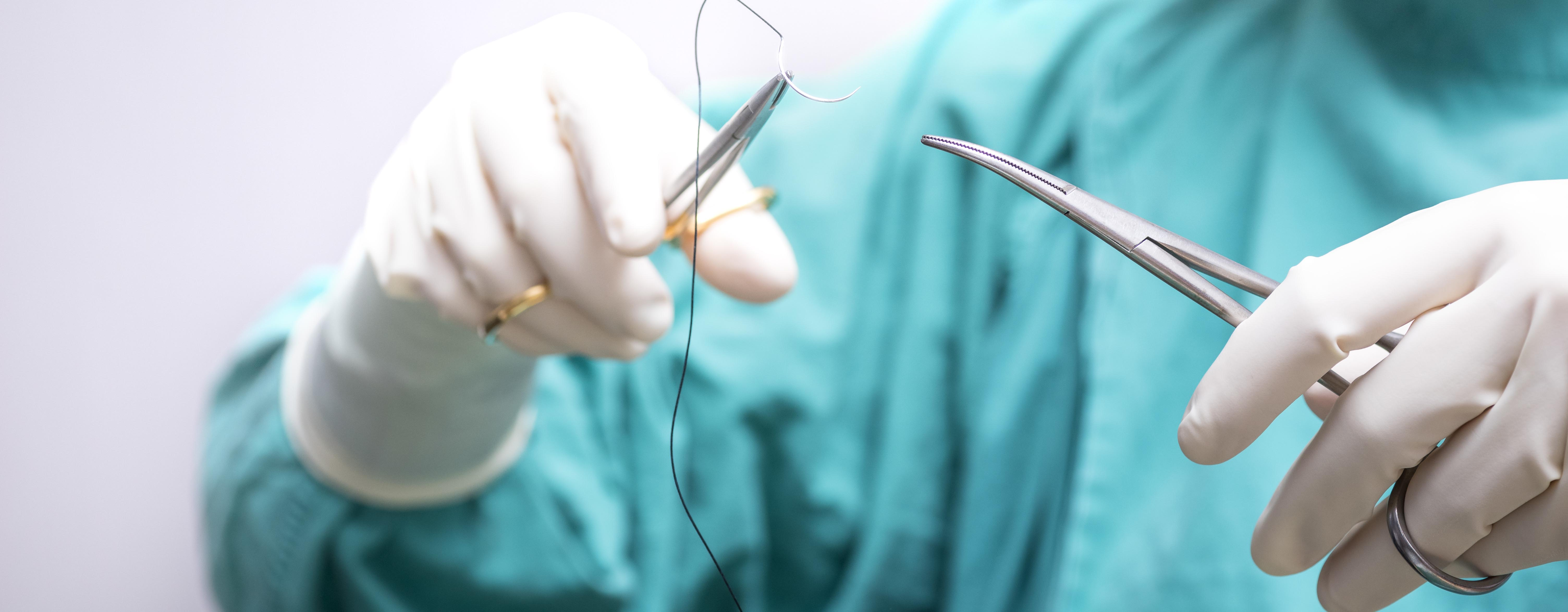 female nurse practitioner surgical forceps holding a suture needle